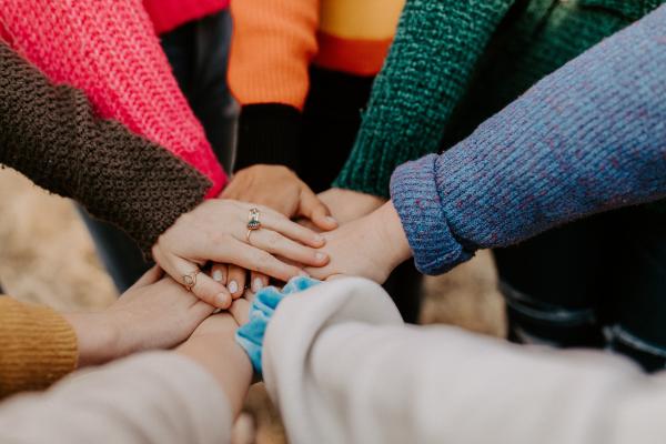 Kuvassa näkyy usean henkilön kädet. Henkilöt seisovat ringissä ja ovat vieneet toisen kätensä keskelle niin, että kädet ovat päällekkäin ja koskettavat toisiaan. Henkilöitä ei muuten näy.