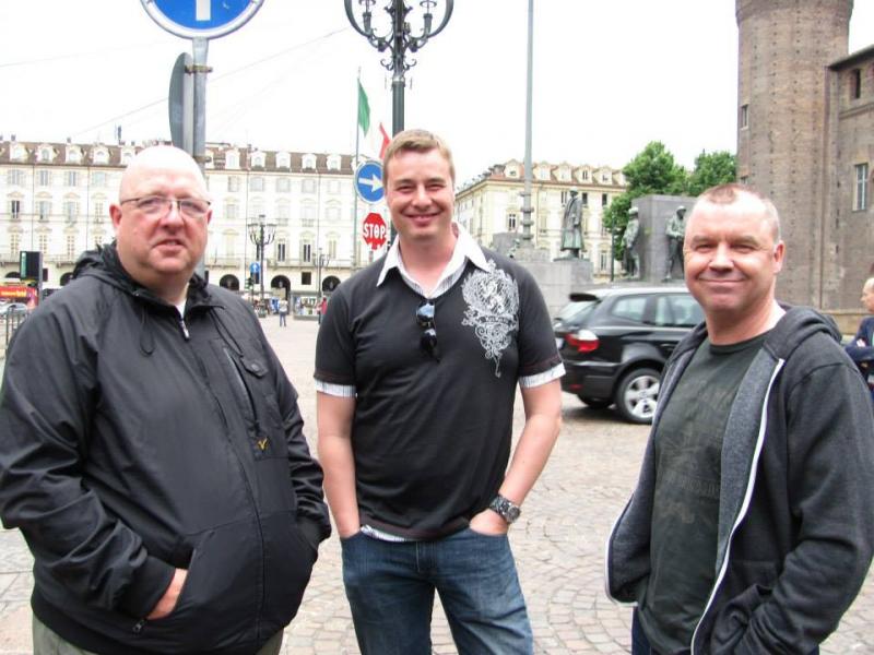 Kolme mieshenkilöä poseeraa kameralle kadulla. Miehet hymyilevät kameralle. He seisovat vierekkäin. Taustalla näkyy liikennemerkkejä ja taempana on isoja rakennuksia.