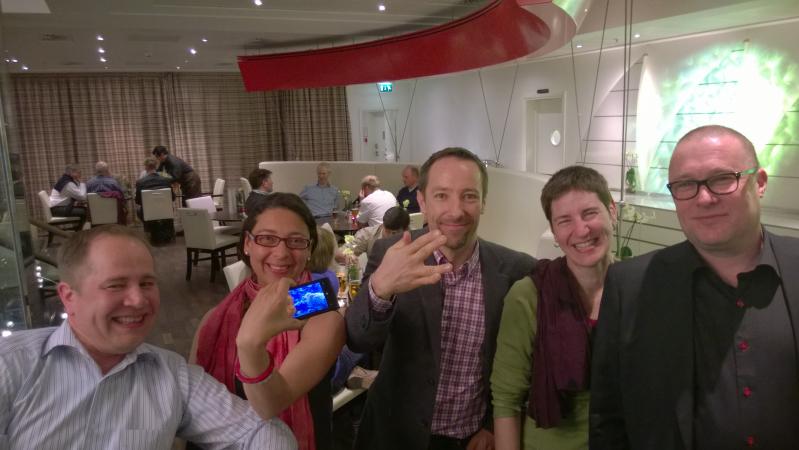 Kuvassa viisi henkilöä hymyilee ja katsoo kuvaan. He seisovat vierekkäin. Yksi henkilöistä pitelee kädessään älypuhelinta niin, että puhelimen sininen näyttö on kuvaan päin. Toinen henkilö näyttää Star Trek -sarjasta tuttua tervehdystä sormillaan. Taustalla näkyy muita henkilöitä, jotka ovat kerääntyneet ruokailutilan pöytien ympärille istumaan.