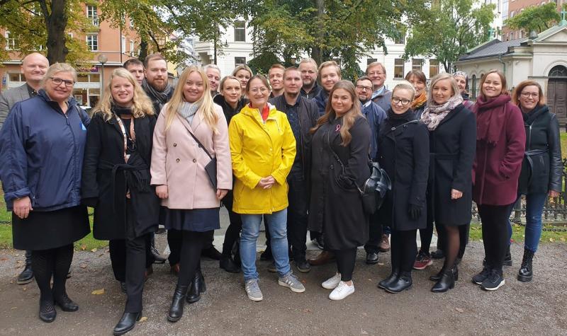 Nordenskolanin henkilöstö ja osallistujat seisovat ulkona ryhmäkuvassa ulkovaatteet päällä. Kuvassa näkyy 17 ihmistä. Henkilöt hymyilevät ja katsovat kuvaan.
