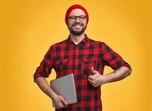 Kuvassa on pipopäinen mies, jolla on toisessa kädessään kannettava tietokone. Hän pitelee sitä kansi kiinni kylkeään vasten. Miehellä on punainen pipo, silmälasit ja parta. Miehellä on yllään puna-musta-raidallinen paita päällään. Kuvan tausta on keltainen.