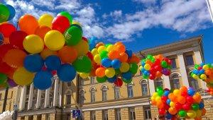 Kuvassa on värikkäitä ilmapalloja, jotka on koottu naruilla nipuiksi niin, että ilmapallot ovat yhtenä sumppuna kiinni toisissaan. Nippuja on useita. Kuva on kadulta keltaisen rakennuksen edestä. Taivas on sininen ja taivaalla näkyy pilvenhattaroita.