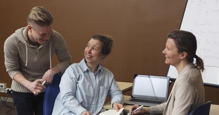 Kuvassa on kolme ihmistä työpöydän ääressä. Kaksi naista istuu työtuoleilla ja mies nojaa toisen naisen takana tämän tuolin selkänojaan. Nainen ja mies hymyilevät toisilleen. Toinen nainen katsoo heihin päin ja hymyilee. Taustalla on fläppitaulu, johon on kirjoitettu tekstiä. Pöydällä on tietokone.