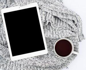 Kuva on mustavalkoinen. Kuvassa on iPad ylhäältä päin kuvattuna jonkin villaisen kankaan päällä. Kankaan päällä on myös kahvikuppi. Kupissa on mustaa kahvia.