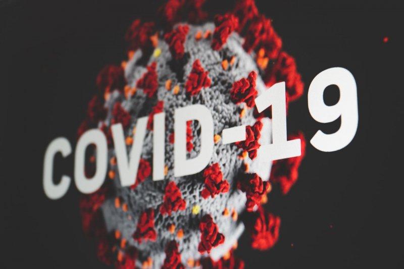 Kuvituskuvassa virusmolekyyli ja teksti covid-19.
