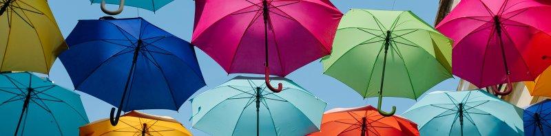 Erivärisiä sateenvarjoja sinistä taivasta vasten.