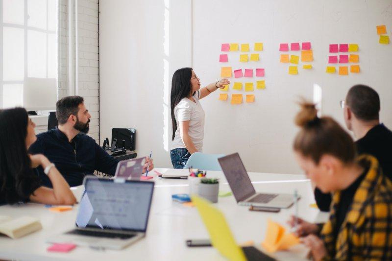 Kuvassa on huone, jossa on iso valkoinen pöytä ja pöydän äärellä ihmisiä. Pöydällä on kannettavia tietokoneita. Taustalla on nainen, joka seisoo seinän vieressä ja katsoo seinälle liimattuja post-it-lappuja. Laput ovat keltaisia, oransseja ja pinkkejä.